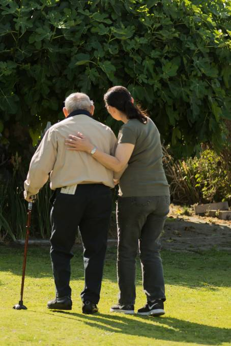 Caregiver guiding an older adult outside