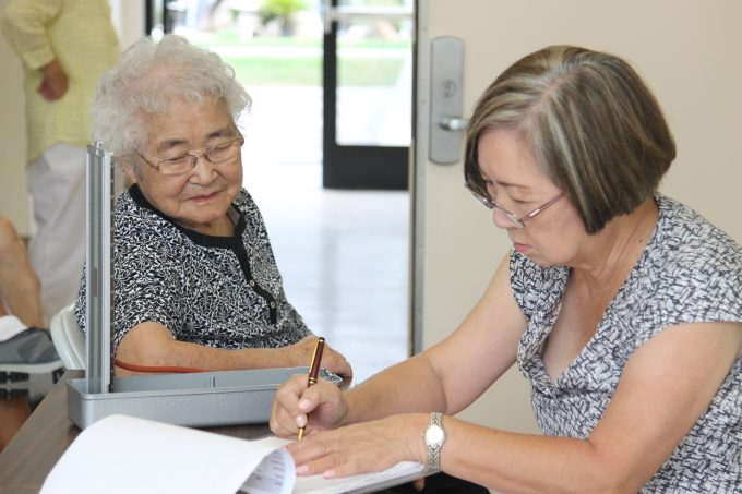 Adult woman filling out paperwork with elderly adult woman