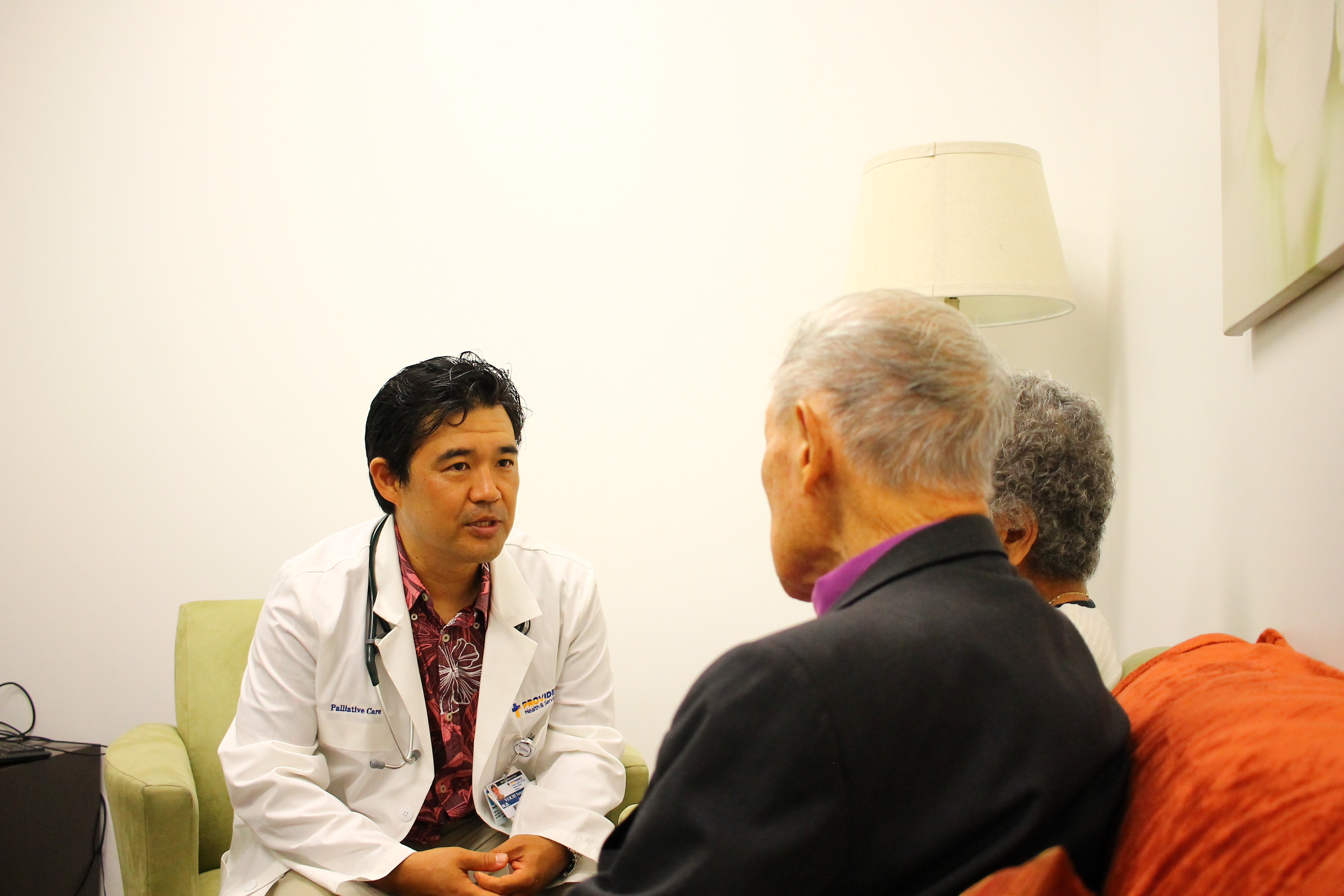 Medical professional speaking to two adults