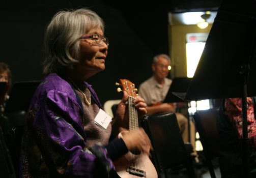 Older adult woman playing the ukulele