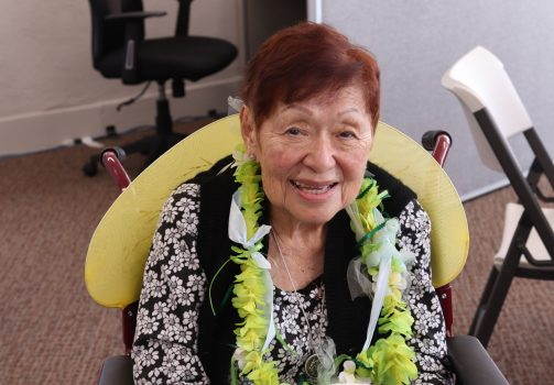 Older adult woman wearing a flower lei around her neck.