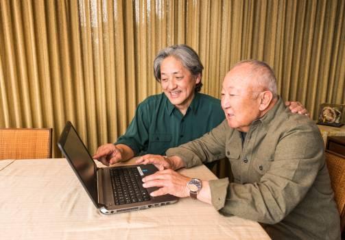 caregiver assisting older adult with laptop