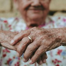 older adult with hands focused
