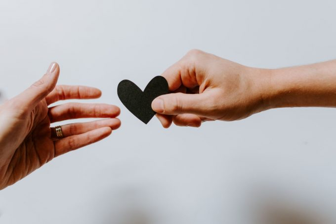 handing a paper heart to another hand