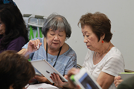 Two adult women looking at a tablet